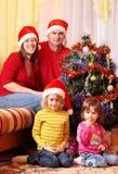 Familie im roten Weihnachtshut Stockbild