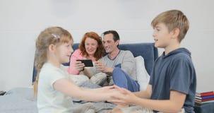 Familie im Schlafzimmer, Eltern, die Zellintelligentes Telefon während Kinderspielspiele zusammen im Morgen verwenden stock footage