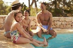 Familie im Urlaub, die durch Pool im Freien sich entspannt lizenzfreie stockfotos