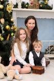Familie im Weihnachtsinnenraum Lizenzfreie Stockbilder