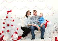 Familie im Weihnachtsraum lizenzfreie stockbilder