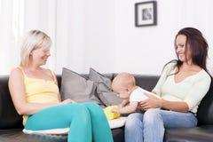 Familie im Wohnzimmer mit Baby. Stockbild