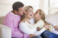 Familie im Wohnzimmer mit junges Mädchen küssendem woma lizenzfreie stockfotos