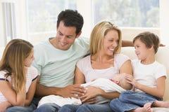 Familie im Wohnzimmer mit Schätzchen stockfotos