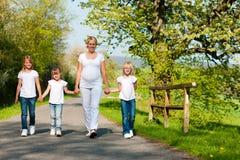 Familie - jonge geitjes en moeder die onderaan een weg lopen Royalty-vrije Stock Afbeeldingen