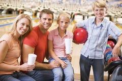Familie in kegelbaan met dranken het glimlachen Stock Fotografie