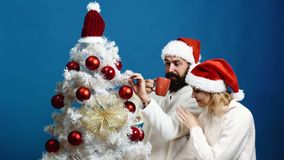 Familie, Kerstmis, de wintervakantie en mensenconcept Het gelukkige paar die Kerstmisboom verfraaien en drinkt thee over blauw stock video