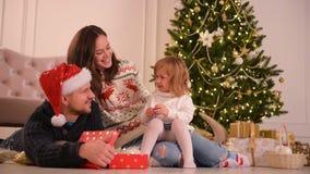 Familie in Kerstmis Santa Hats Lying On Floor Ouders en Baby die Pret in Slaapkamer hebben Mensen die thuis ontspannen De winter stock videobeelden