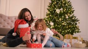 Familie in Kerstmis Santa Hats Lying On Floor Ouders en Baby die Pret in Slaapkamer hebben Mensen die thuis ontspannen De winter stock video