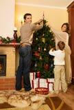 Familie in Kerstmis verfraaid huis Stock Afbeeldingen
