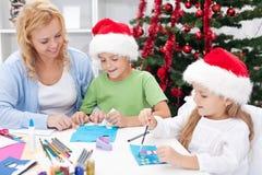 Familie in Kerstmistijd die groetkaarten maakt Royalty-vrije Stock Foto