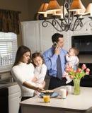 Familie in keuken. Stock Afbeelding