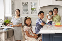 Familie in Keuken die Karweien doen en Digitale Apparaten met behulp van Royalty-vrije Stock Foto