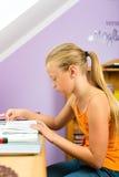 Familie - kind dat thuiswerk doet Stock Afbeelding