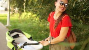 Familie, kind en ouderschapconcept - gelukkige moeder die met babywandelwagen lopen in park van rug stock video