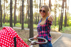 Familie, Kind und Elternschaftskonzept - glückliche Mutter mit Spaziergänger im Park lizenzfreie stockbilder