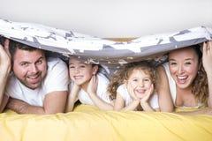 Familie, Kinder und Hauptkonzept - glückliche Familie mit zwei Kindern unter Decke zu Hause Stockfotografie