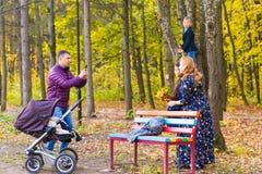 Familie, Kindheit, Jahreszeit, Technologie und Leutekonzept - glückliche Familie, die im Herbstpark fotografiert stockbild