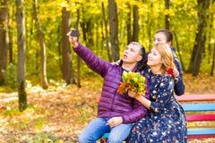 Familie, Kindheit, Jahreszeit, Technologie und Leutekonzept - glückliche Familie, die im Herbstpark fotografiert stockfoto