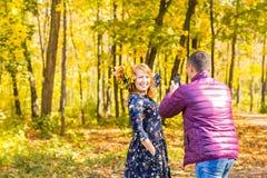 Familie, Kindheit, Jahreszeit, Technologie und Leutekonzept - glückliche Familie, die im Herbstpark fotografiert stockfotografie