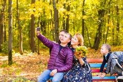 Familie, Kindheit, Jahreszeit, Technologie und Leutekonzept - glückliche Familie, die im Herbstpark fotografiert stockfotos