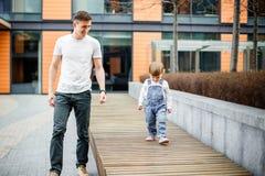 Familie, Kindheit, Vaterschaft, Freizeit und Leutekonzept - glücklicher junger Vater und kleine Tochter schlendern durch die Stra lizenzfreies stockfoto
