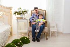 Familie, Kindheit, Vaterschaft, Tätigkeit und Leutekonzept - glücklicher Vater und kleiner Sohn, die zu Hause spielt lizenzfreies stockbild