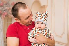 Familie, Kindheit, Vaterschaft und Leutekonzept - glücklicher Vater und Babysohn zu Hause lizenzfreies stockbild