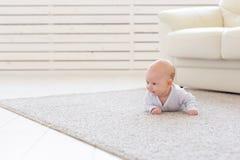 Familie, Kindheitskonzept - Abschluss herauf Porträt der hübschen Babylüge auf dem Boden stockbild