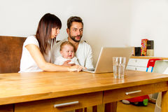 Familie on a laptop. Young happy familie with baby on a computer Stock Photos