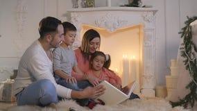 Familie las das Buch, das auf Sofa vor Kamin in Weihnachten verziertem Hausinnenraum sitzt stock video