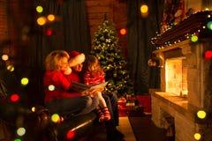 Familie las die Geschichten, die auf Sofa vor Kamin in Weihnachten verziertem Hausinnenraum sitzen lizenzfreie stockfotos