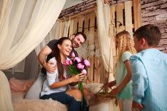 Familie macht die Überraschungsmutter, die Geschenke von Blumen gibt Stockfotografie