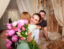 Familie macht die Überraschungsmutter, die Geschenke von Blumen gibt Lizenzfreie Stockfotos