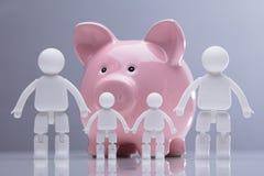 Familie Menselijke Cijfers die zich in Front Of Pink Piggy Bank bevinden royalty-vrije stock afbeeldingen