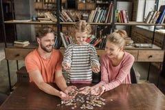 Familie met één kind het spelen met raadsels thuis Stock Foto's