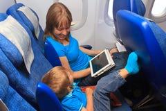 Familie met aanrakingsstootkussen in vliegtuig Stock Fotografie