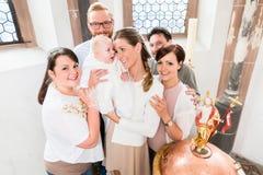 Familie met baby status rond de doopdoopvont Stock Fotografie