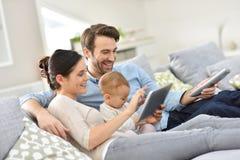 Familie met babyzitting op bank die tablet gebruiken royalty-vrije stock foto