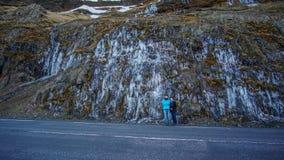 Familie met bevroren de reisscène van de watervalweg in IJsland Royalty-vrije Stock Foto's