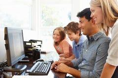 Familie met computer in huisbureau Stock Afbeeldingen