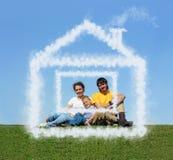 Familie met de wolkenhuis van de zoonszitting op weide Royalty-vrije Stock Afbeeldingen