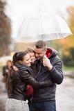 Familie met dochter onder de paraplu'sgang op regenachtige dag Stock Afbeeldingen