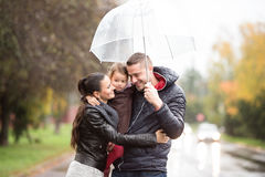 Familie met dochter onder de paraplu'sgang op regenachtige dag Stock Foto's
