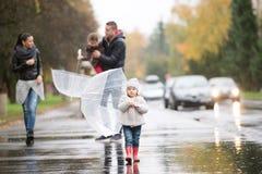Familie met dochters onder de paraplu's Gang op regenachtige dag Royalty-vrije Stock Afbeeldingen