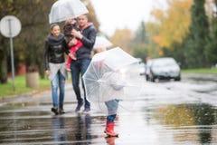 Familie met dochters onder de paraplu's Gang op regenachtige dag Stock Foto's