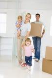 Familie met doos die zich in het nieuwe huis glimlachen beweegt Stock Afbeeldingen
