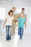 Familie met dozen die zich in het nieuwe huis glimlachen bewegen Stock Foto's