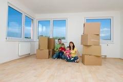 Familie met dozen in nieuw huis stock foto's