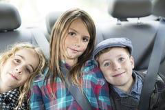 Familie met drie jonge geitjes in een auto royalty-vrije stock foto's